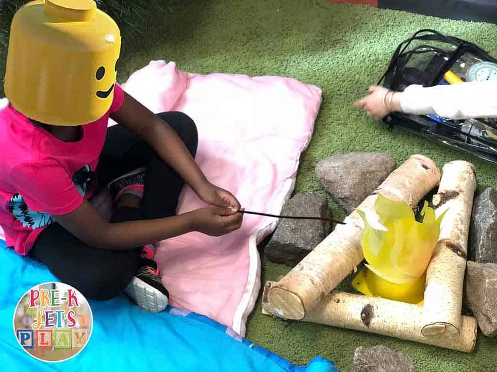 A student is roasting marshmallows under a campfire for pretend play. She is enjoying this dramatic play camping area.