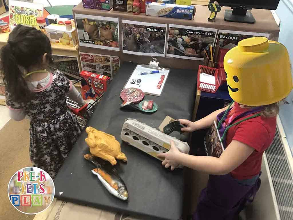 Kids playing grocery store as pretend play in dramatic play area. One kid is role playing as a cashier by scanning pretend food items. The other student is role playing as the customer by placing pretend food on the checkout belt.