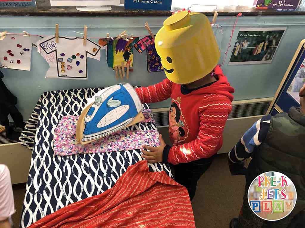 A student ironing clothes for pretend play in laundromat dramatic play area.