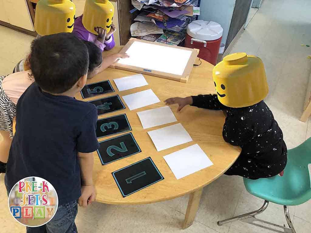 A group of kids are playing a number sense game together. This game is called x-ray vision. Learning through play activities like this make preschool fun.