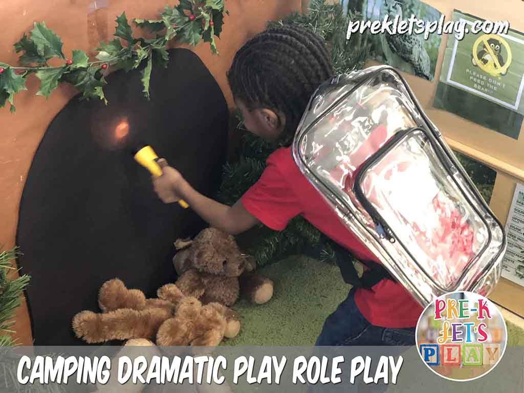 Kids love to role play in this dramatic play camping theme. This student using a flashlight and pretending to go hiking into a pretend play bear cave.