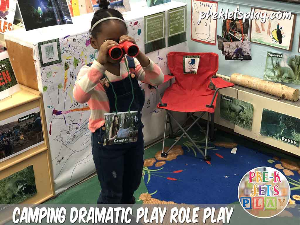 Student role playing as a camper in in this dramatic play camping area . She enjoys using binoculars to go bird watching and looking at other woodland animals for pretend play area.