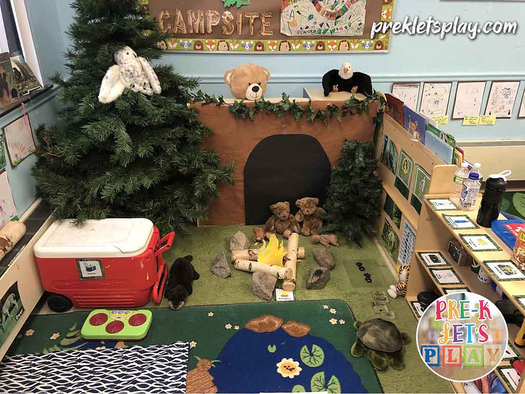 Students love to play and learn inside this camping dramatic play theme. This pretend play area supports imaginative preschool play and features signs, props, and classroom decor to make this space look like a campsite and woodlands.
