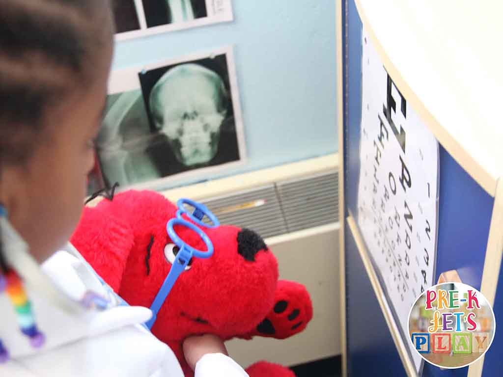 Child playing in the pet vet dramatic play area. She is having so much preschool fun playing the role of doctor. She is a;sp learning through play by help pets read the eye chart.