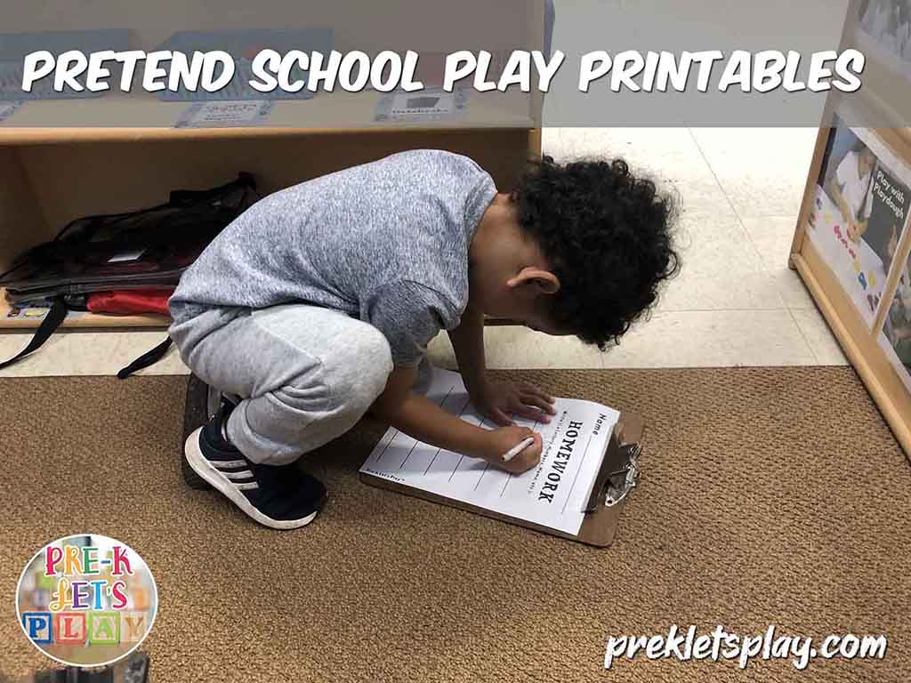 Student writing in pretend school dramatic play. He is doing homework for pretend play. This is a great writing activity.