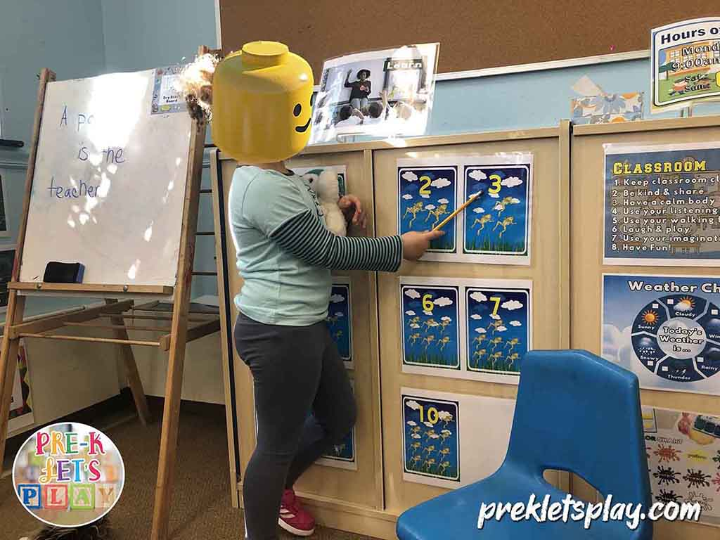 Student in dramatic play pretending to teach numbers. This student enjoys teaching preschool for pretend play.