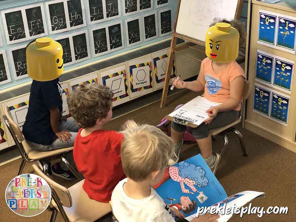 Students in pretend school dramatic play. One is a teacher is teaching preschool and taking attendance. The other kids are pretending to be her students.
