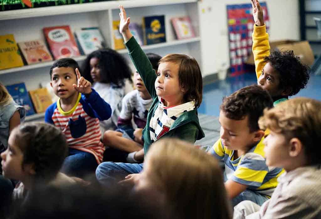 Kids are raising their hand during circle time. They are ready to play and learn through preschool activities.